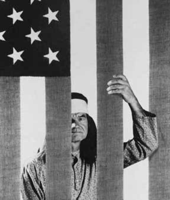 native american trapped in jail behind stripes of american flag